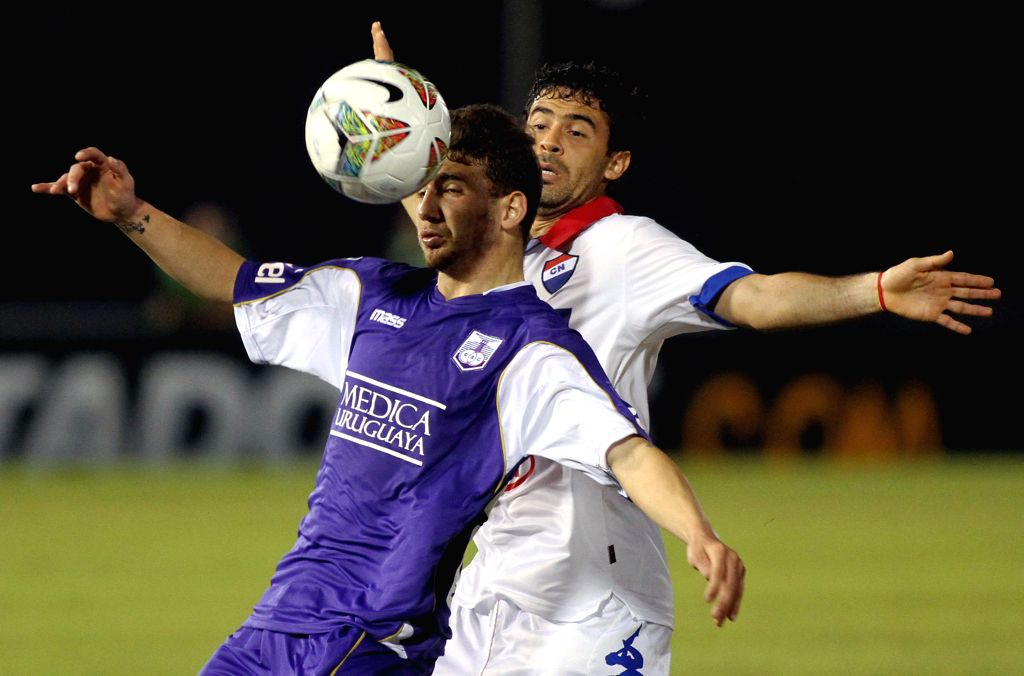 Julian Benitez (BACK) of Paraguay's Nacional vies for the ball with Enrique Echeverri of Uruguay's Defensor Sporting during the first leg of Libertadores Cup ...