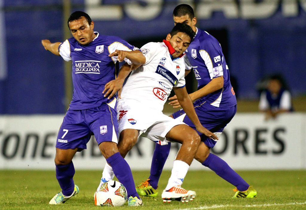 Silvio Torales (C) of Paraguay's Nacional vies for the ball with Juan Carlos Amado (L) of Uruguay's Defensor Sporting during the first leg of Libertadores Cup ...