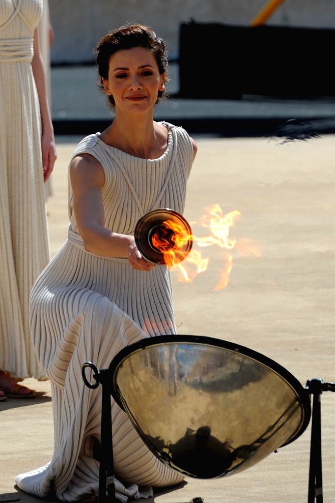 Greek actress Katerina Lehou, playing the role of high priestess, lights the torch with the Olympic Flame during a handover ceremony at Panathenaean Stadium in ... - Katerina Lehou