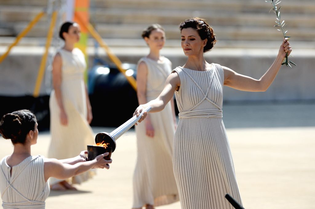Greek actress Katerina Lehou (R), playing the role of high priestess, lights the torch with the Olympic Flame during a handover ceremony at Panathenaean Stadium in . - Katerina Lehou
