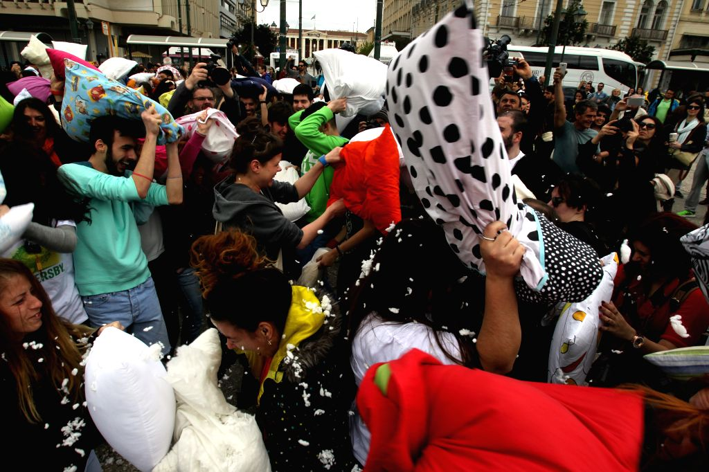 People take part in a pillow fight marking the International Pillow Fight Day in Athens, Greece, on April 5, 2015. (Xinhua/Marios Lolos)