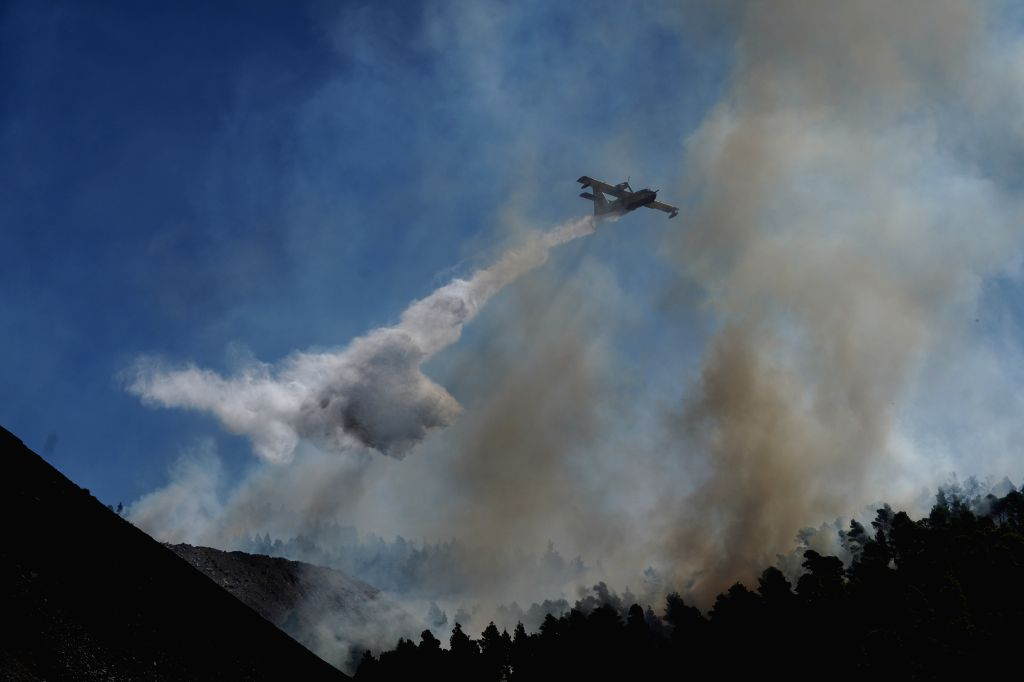 ATHENS, Aug. 15, 2019 - An airplane sprays over an active fire front near Stavros village, on Evia island, Greece, on Aug. 14, 2019. Amid ongoing efforts to extinguish a destructive wildfire, Greek ... - Kyriakos Mitsotakis