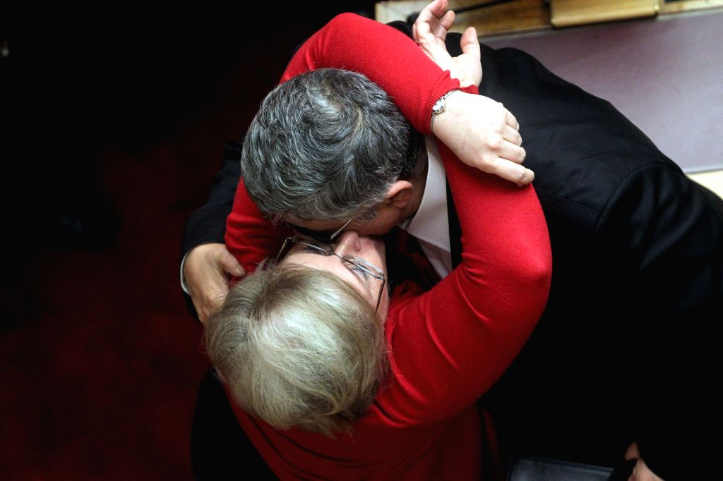 The leader of the far-right political party Golden Dawn Nikos Michaloliakos (R), is kissed by his wife and lawmaker Eleni Zaroulia during the first round of voting ..