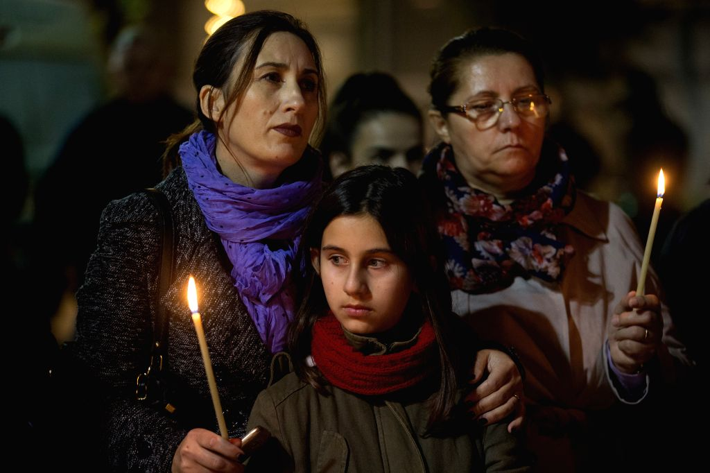 ATHENS, Dec. 3, 2019 - People hold candles during an event in memory of the victims of an earthquake in Athens, Greece, on Dec. 3, 2019. A week after a devastating quake hit Albania, Greeks joined ...