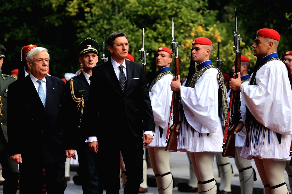 ATHENS, Dec. 4, 2018 - Greek President Prokopis Pavlopoulos (L, front) and Slovenian President Borut Pahor  (R, front) inspect the guard of honor during a welcome ceremony at the presidential mansion ...
