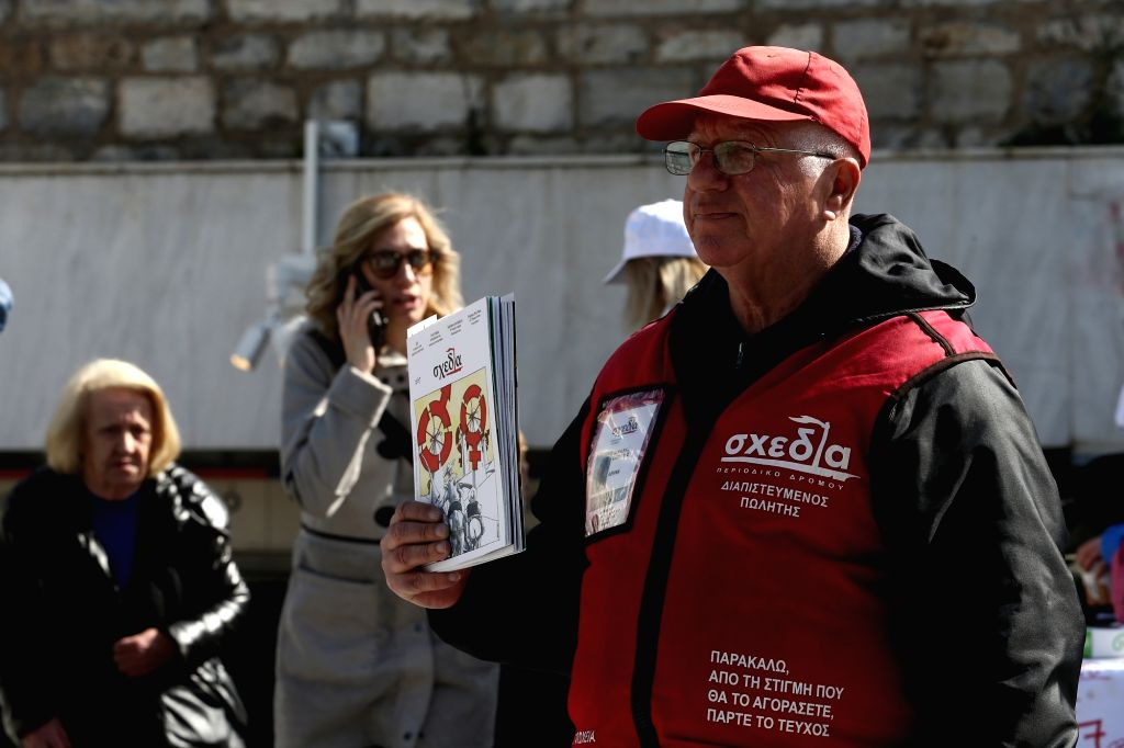 "ATHENS, Feb. 24, 2018 - Michalis Samolis (R), an unemployed man, sells the ""Shedia"" magazine on a street of central Athens, Greece, on Feb. 19, 2019. ""Shedia"" magazine in Athens, ..."