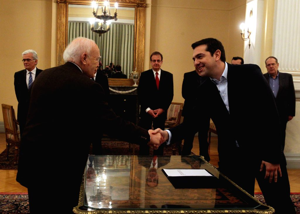 SYRIZA party leader Alexis Tsipras (R), shakes hands with President of Greek President Karolos Papoulias at the Presidential Palace in Athens, Greece, Jan. 26, 2015.