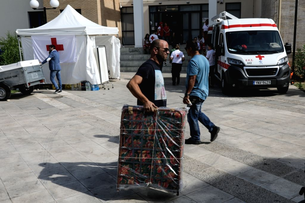 ATHENS, July 26, 2018 - A man carries a folding bed for people affected by wildfires to the city hall of Rafina, east of Athens, Greece, on July 26, 2018. As Greece mourned its deadliest tragedy ...