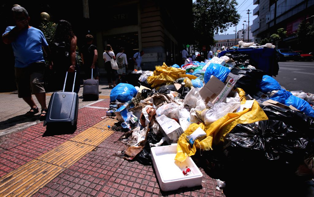 ATHENS, June 26, 2017 - People walk past a pile of garbage in Athens, Greece, on June 26, 2017. Tons of garbage are piling up in Athens and other major cities as a nationwide protest against job cuts ...