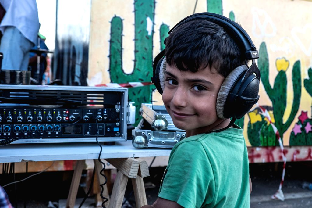ATHENS, May 10, 2017 - A refugee child listens to the performance given by the Municipal Youth Orchestra of Caracas from Venezuela at?Skaramangas refugee camp near Piraeus, Greece, on May 10, 2017. ...