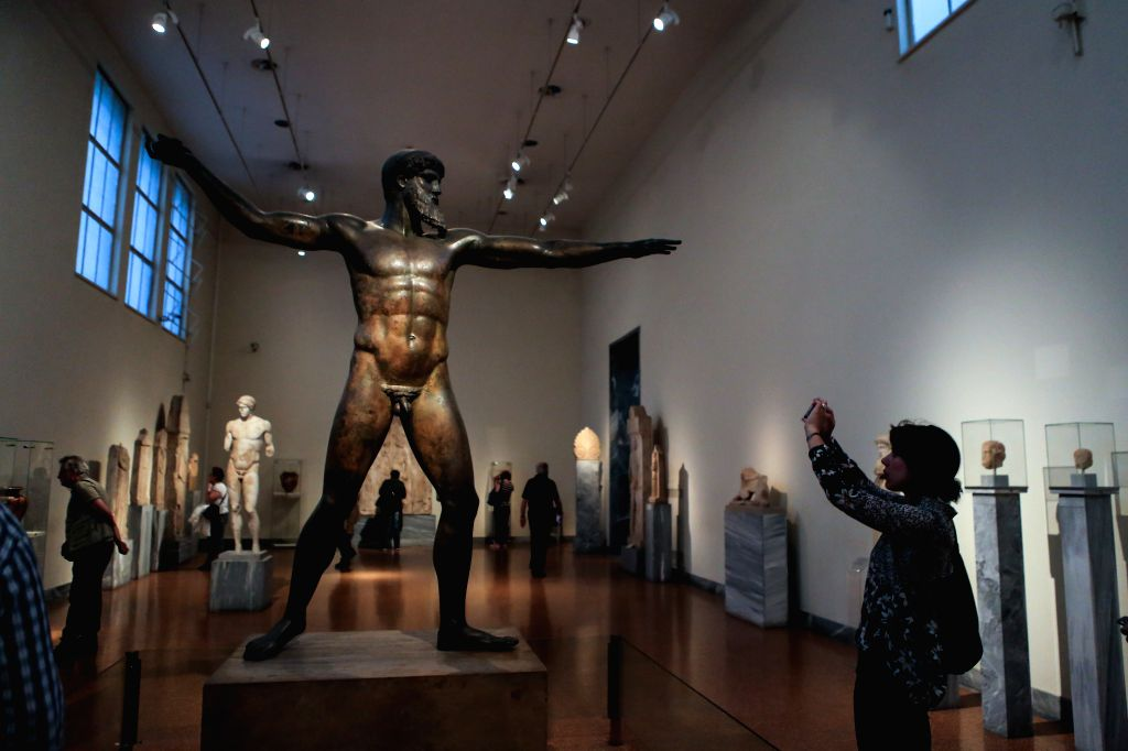 ATHENS, May 20, 2016 - A woman takes pictures of a bronze statue of Zeus dated back to around 460 B.C. at the National Archaeological Museum in Athens, Greece on May 18, 2016. Among numerous ...