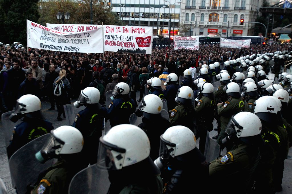 Riot police stand guard as Greek people attend a march in memory of the 1973 student uprising in Athens, Greece, Nov, 17, 2014. Riot police clashed with protesters on Monday as more than ...