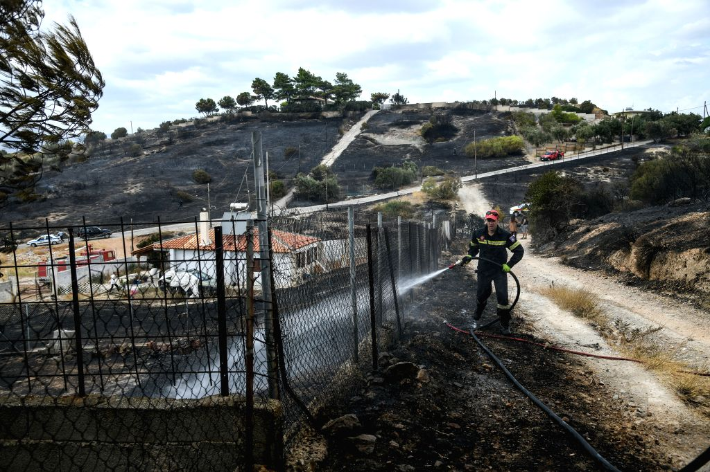 ATHENS, Sept. 13, 2019 - A firefighter tries to put out a wildfire in Saronida, Greece, on Sept. 13, 2019. A wildfire which broke out at the coastal resort of Saronida near Athens on Friday has been ...