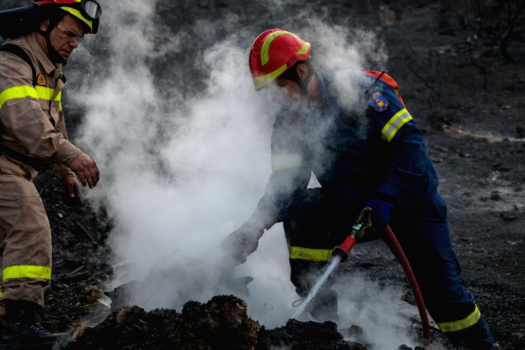 ATHENS, Sept. 13, 2019 - Firefighters try to put out a wildfire in Saronida, Greece, on Sept. 13, 2019. A wildfire which broke out at the coastal resort of Saronida near Athens on Friday has been put ...