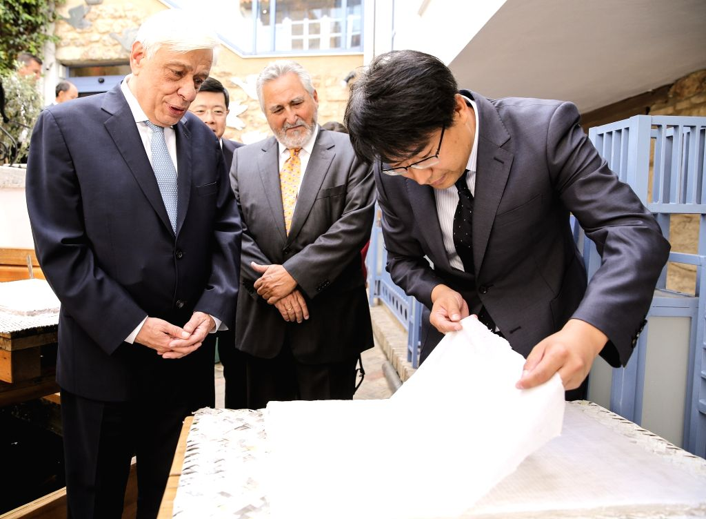 ATHENS, Sept. 27, 2017 - Greek President Prokopis Pavlopoulos (L, front) watches a demonstration of paper making at an exhibition of ancient Chinese science and technology at Herakleidon museum just ...