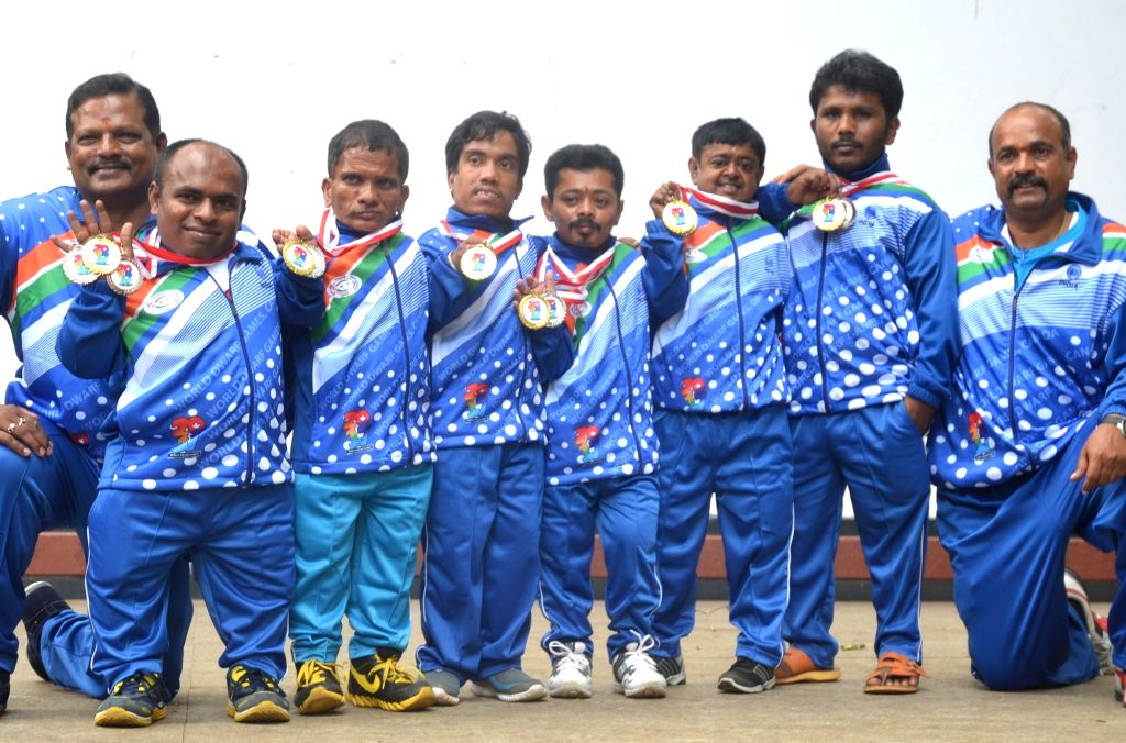 Athletes of the Indian contingent of the World Dwarf Games along with their coach and manager Shivananda Gunjal display their medals after winning 37 medals at the 7th edition of the World ...