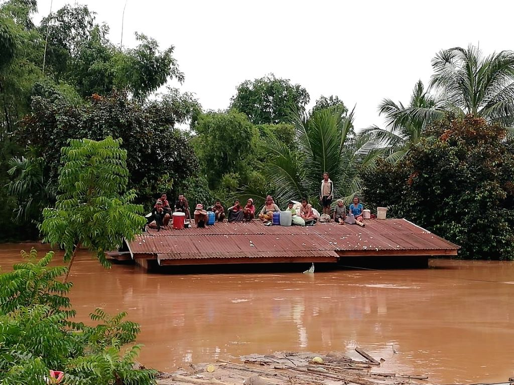 ATTAPEU (LAOS), July 24, 2018 Villagers are seen stranded on rooftop of a house after an under-construction dam collapsed in Attapeu, Laos, on July 24, 2018. At least two people are ...