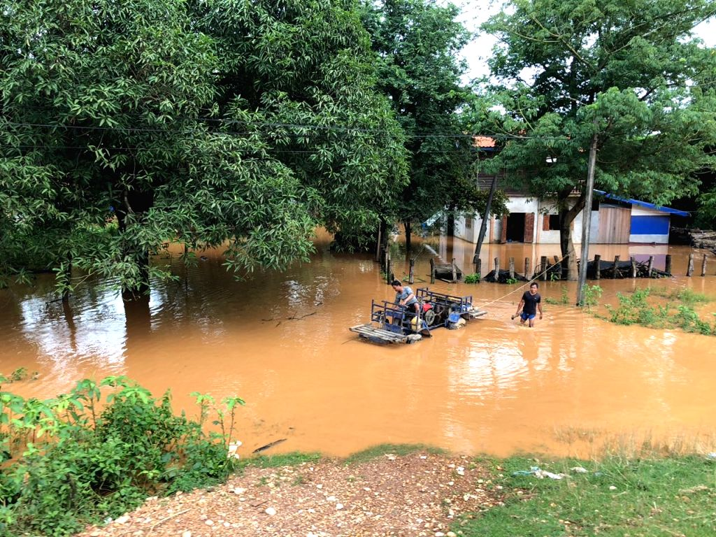 ATTAPEU (LAOS), July 24, 2018 Villagers wade through a flooded area after an under-construction dam collapsed in Attapeu, Laos, on July 24, 2018. At least two people are confirmed dead as ...