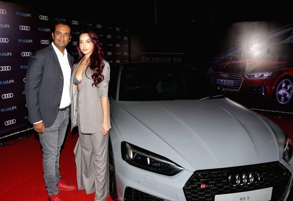 Audi India Head Rahil Ansari and actress Nora Fatehi pose with the Audi RS 5 Coupe at Audi Peaklife Fashion Capsule in New Delhi, on April 5, 2019. - Nora Fatehi