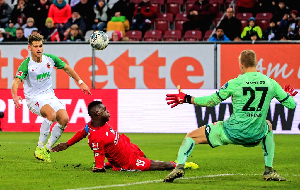AUGSBURG, Dec. 8, 2019 - Florian Niederlechner (L) of Augsburg takes a shot under the defense from Moussa Niakhate (C) of Mainz during a German Bundesliga match between FC Augsburg and 1.FSV Mainz 05 ...