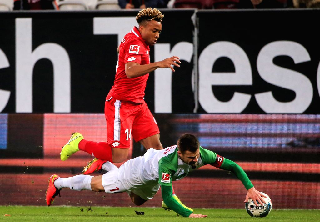 AUGSBURG, Dec. 8, 2019 - Pierre Kunde Malong (top) of Mainz vies with Daniel Baier of Augsburg during a German Bundesliga match between FC Augsburg and 1.FSV Mainz 05 in Augsburg, Germany, on Dec. 7, ...