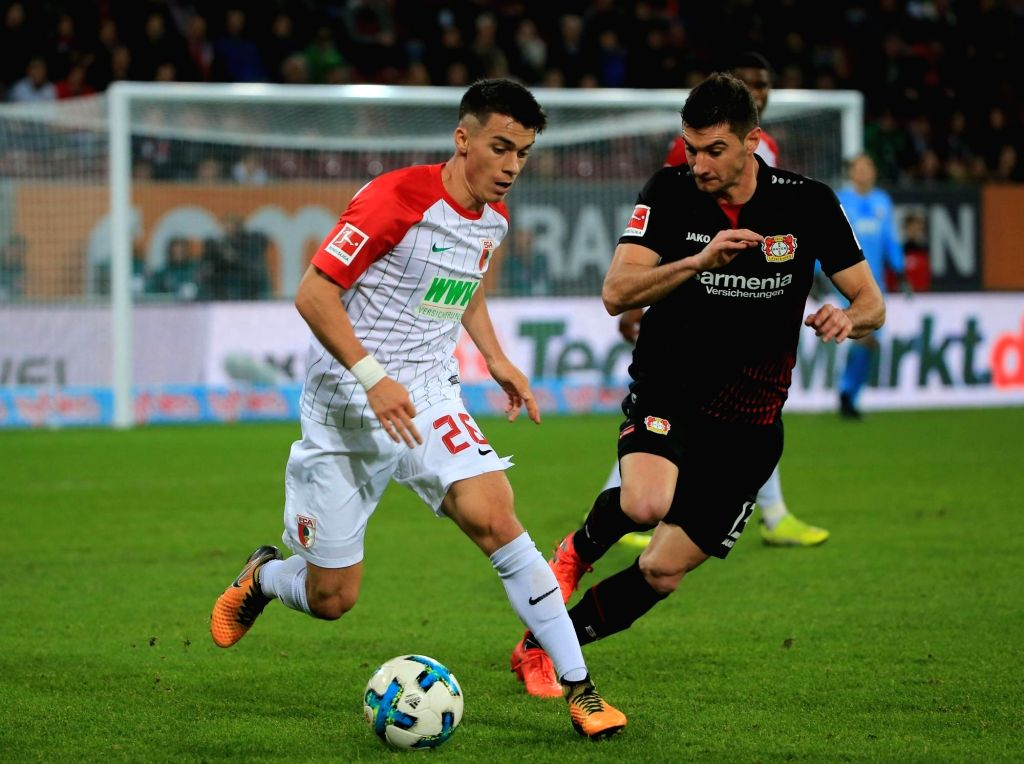 AUGSBURG, Nov. 5, 2017 (Xinhua) -- Augsburg's Erik Thommy (L) controls the ball under the defense from Leverkusen's Lucas Alario during a German Bundesliga match between FC Augsburg and Bayer 04 Leverkusen, in Augsburg, Germany, on Nov. 4, 2017. The