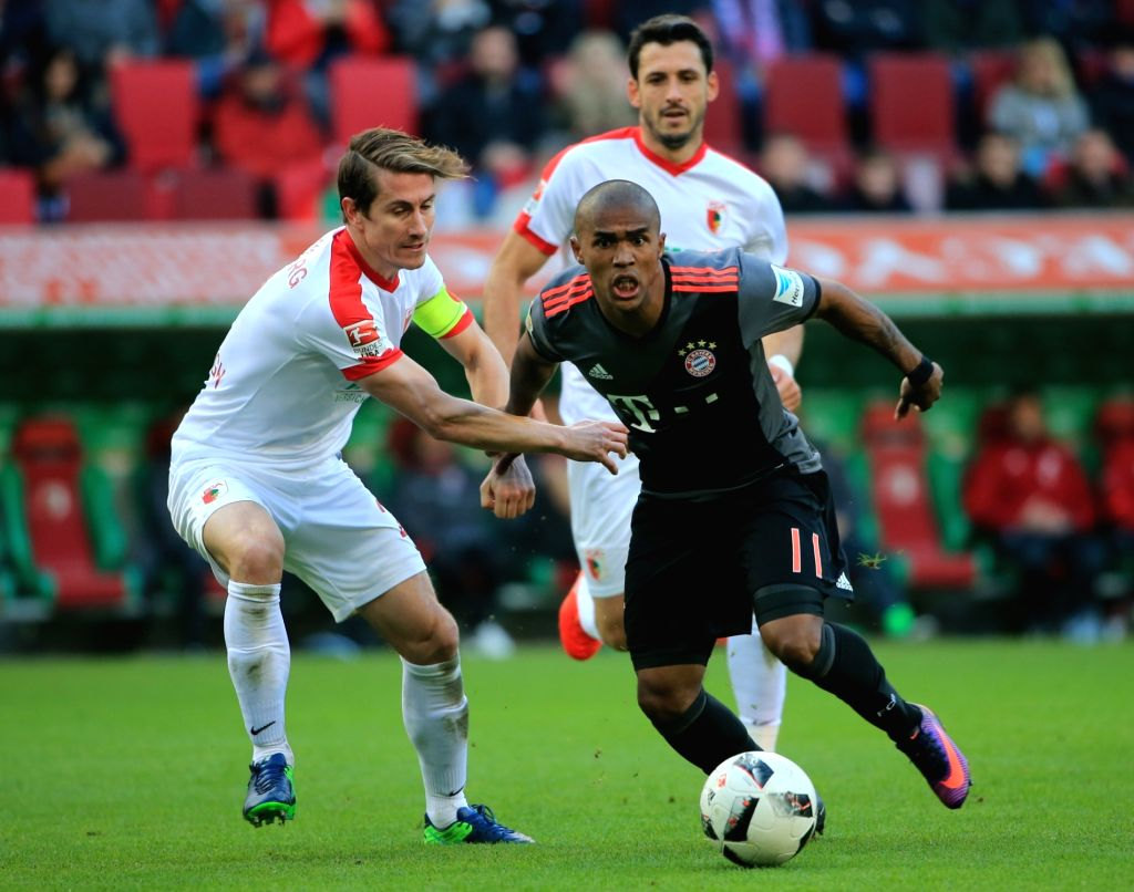 AUGSBURG, Oct. 30, 2016 - Bayern Munich's Douglas Costa (R) vies for the ball with FC Augsburg's Paul Verhaegh during the German Bundesliga soccer match between FC Augsburg and FC Bayern Munich in ...