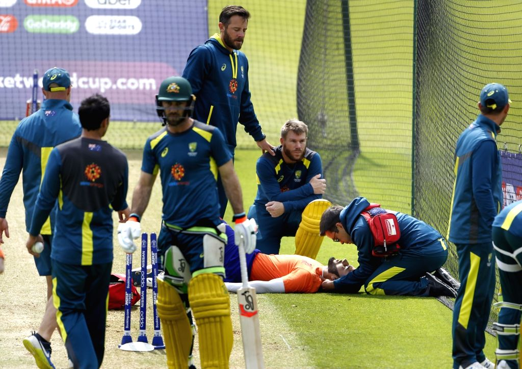 Australia's David Warner asks for medial help after hitting a net bowler on his head during a practice session ahead of their 2019 ICC Cricket World Cup match against India, at the Oval in ...