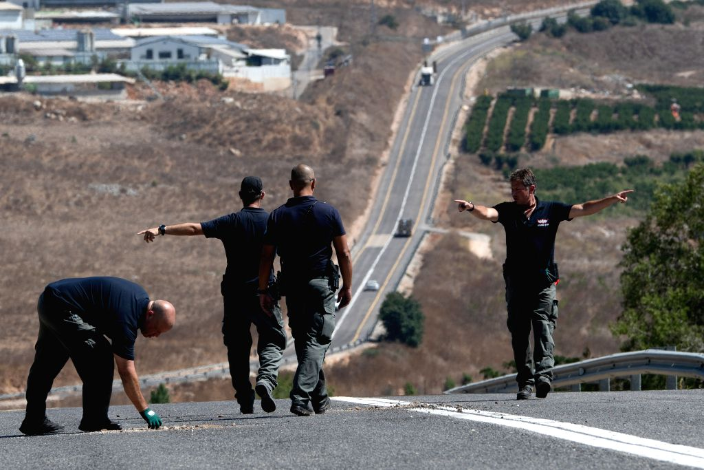 AVIVIM (ISRAEL), Sept. 2, 2019 Members of Israeli security forces check a damaged road in the Israeli village of Avivim, close to the border with Lebanon, on Sept. 2, 2019. Tensions have ...