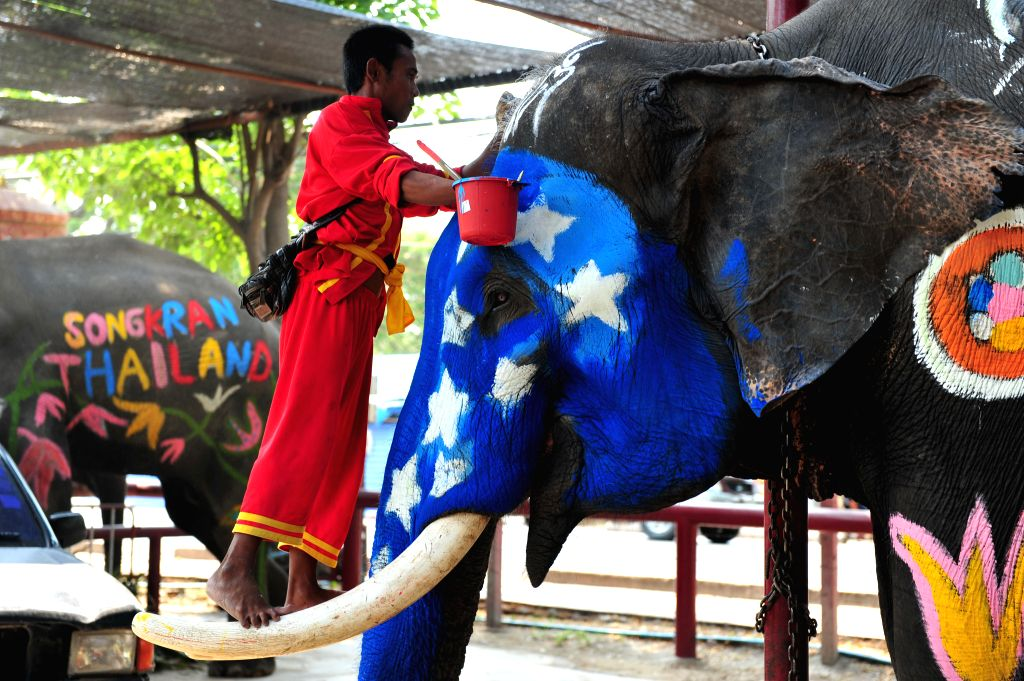 A worker paints an elephant during a celebration of the upcoming Songkran festival in Ayutthaya province, Thailand, April 10, 2015. Songkran, also known as the ...