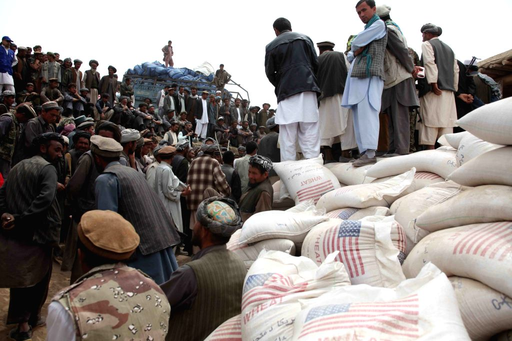 Afghans wait to receive relief food after a landside in Badakhshan province, northern Afghanistan, May 4, 2014. The deadly landslide occurred Friday in the ...