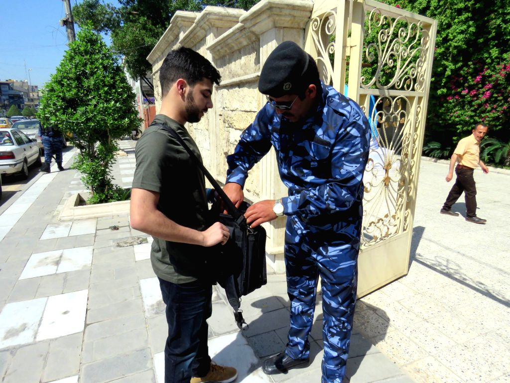 BAGHDAD, April 16, 2017 - An Iraqi policeman checks the bag of a Christian worshipper for the Easter service at the Virgin Mary church in Baghdad's Karrada neighbourhood on April 16, 2017.