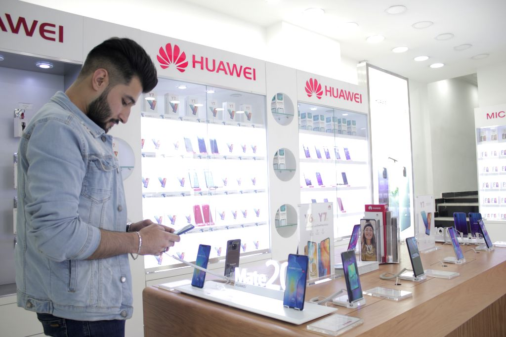 BAGHDAD, April 9, 2019 - An Iraqi customer looks at a Chinese smart phone in Baghdad, Iraq, March 30, 2019. Over the past seven years, the Iraqi customers have gradually been attracted to the Chinese ...
