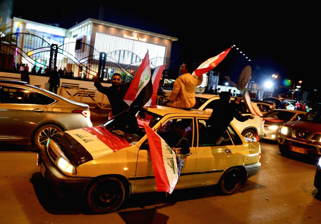 BAGHDAD, Dec. 10, 2018 - People wave Iraqi flags in a street in Baghdad, capital of Iraq, Dec. 10, 2018. Iraqis celebrated the Victory Day on Monday, one year after the announcement of full ...