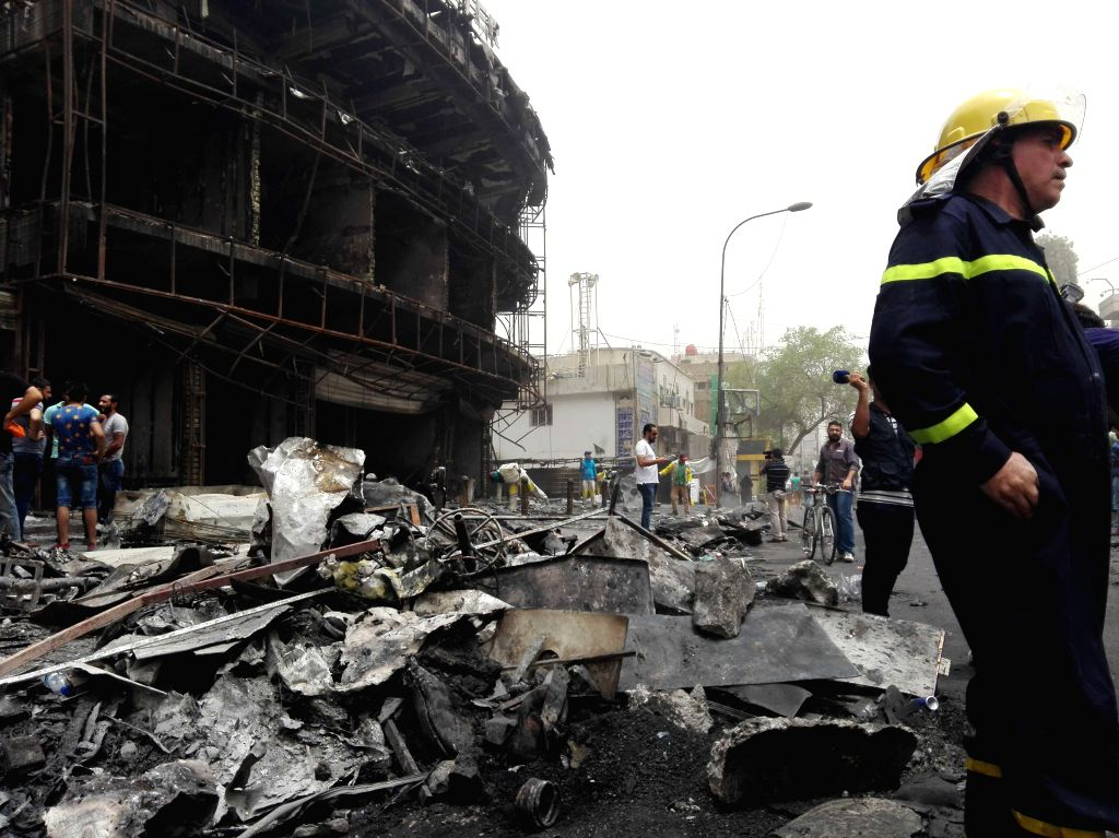 BAGHDAD, July 3, 2016 - A firefighter reacts at the car bomb attack site in Karrada-Dakhil district of southern Baghdad, Iraq, July 3, 2016. Death toll of the suicide car bomb attack at a crowded ...