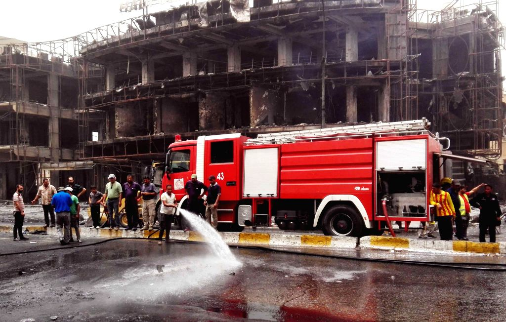 BAGHDAD, July 3, 2016 - Firefighters clean the car bomb attack site in Karrada-Dakhil district of southern Baghdad, Iraq, July 3, 2016. Death toll of the suicide car bomb attack at a crowded ...