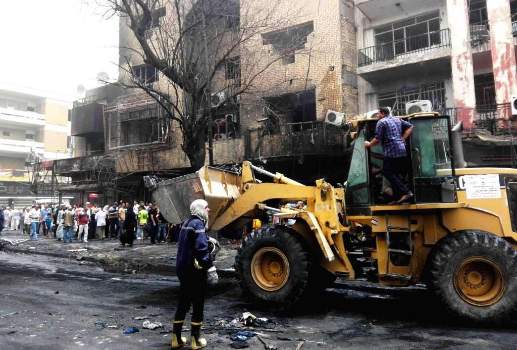 BAGHDAD, July 3, 2016 - Workers clean the car bomb attack site in Karrada-Dakhil district of southern Baghdad, Iraq, July 3, 2016. Death toll of the suicide car bomb attack at a crowded commercial ...
