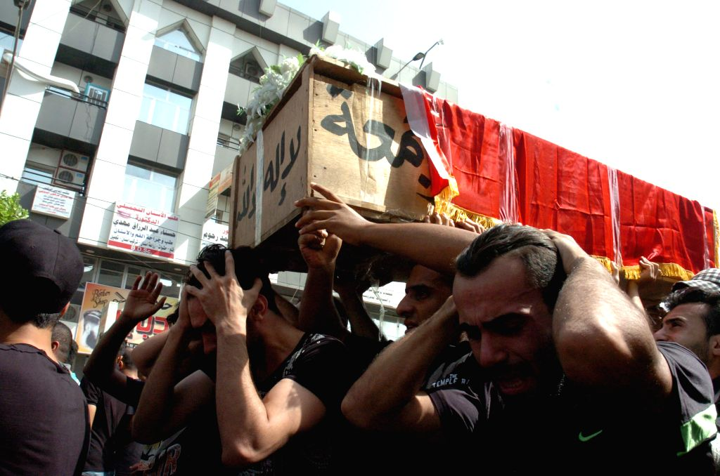 BAGHDAD, July 5, 2016 - People carry a coffin as they mourn for the victims killed in Sunday's car bombing attacks in Karrada-Dakhil district in southern Baghdad, Iraq, on July 5, 2016. Iraq began on ...