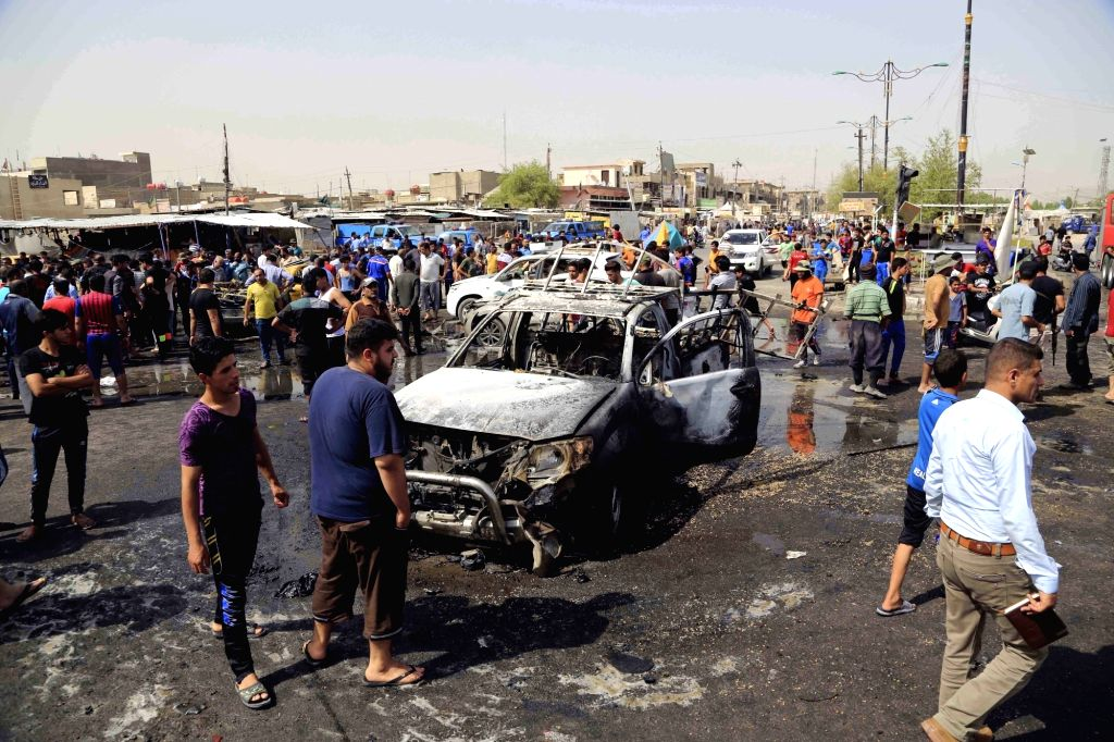 BAGHDAD, May 17, 2016 - People gather at the expolsion site after an attack killing around 16 people and wounding 53 others in Sadr City in eastern Baghdad, Iraq, on May 17, 2016.