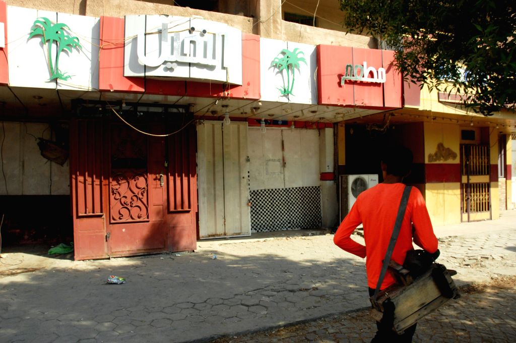 BAGHDAD, Oct. 23, 2016 - An Iraqi man walks past a closed liquor store in the capital Baghdad on Oct. 23, 2016. Iraq's parliament on Oct. 22, voted to ban the sale, import and production of alcohol.