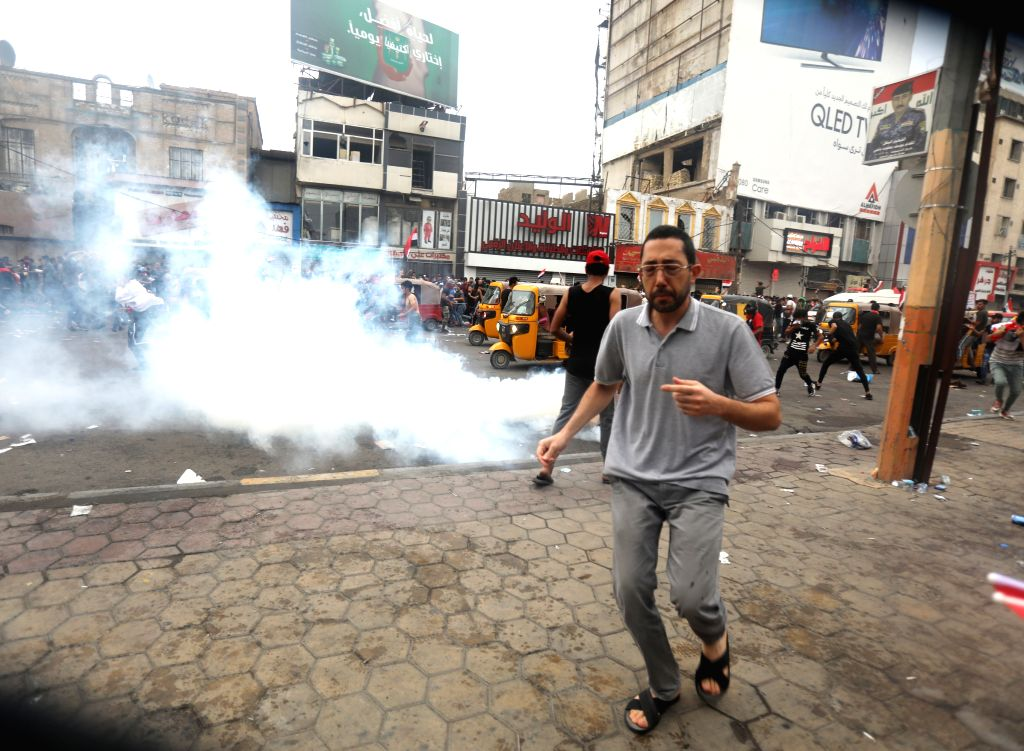 BAGHDAD, Oct. 25, 2019 - A protester runs for cover from tear gas canisters during a protest in Baghdad, Iraq, on Oct. 25, 2019. Hundreds of protesters rallied Friday in some Iraqi cities including ...