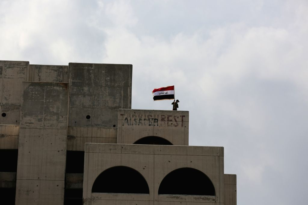 BAGHDAD, Oct. 25, 2019 - A protester waves an Iraqi flag on the rooftop of a building at the Tahrir Square in Baghdad, Iraq, on Oct. 25, 2019. Hundreds of protesters rallied Friday in some Iraqi ...