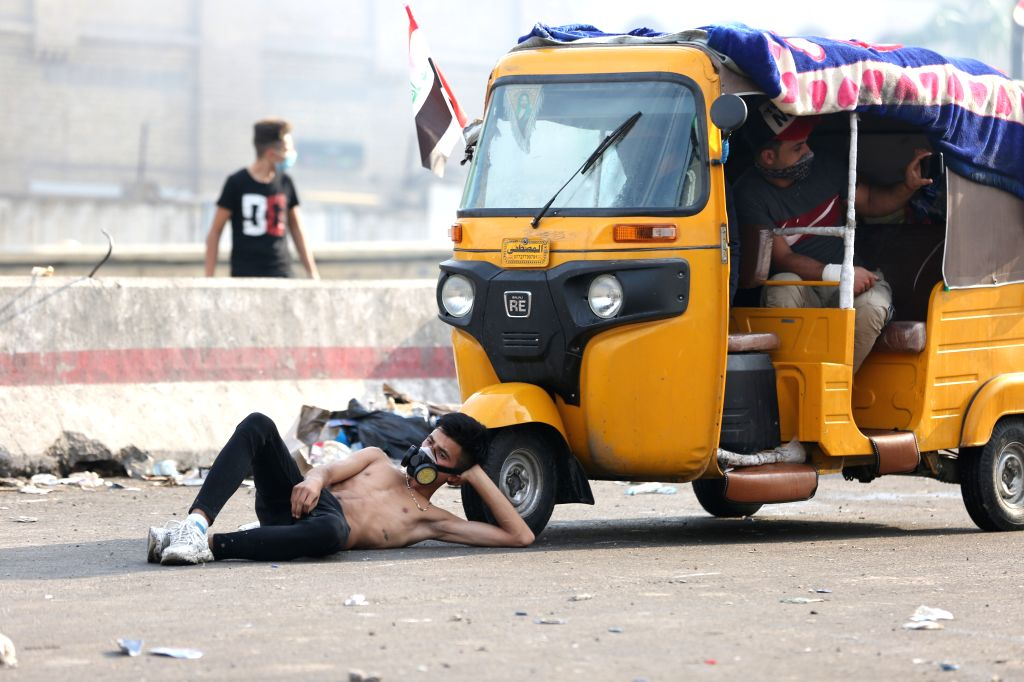 BAGHDAD, Oct. 27, 2019 - A protester takes a rest by a tuk-tuk during a protest at Tahrir square in Baghdad, Iraq, on Oct. 27, 2019. The Iraqi authorities said on Sunday that the death toll from the ...