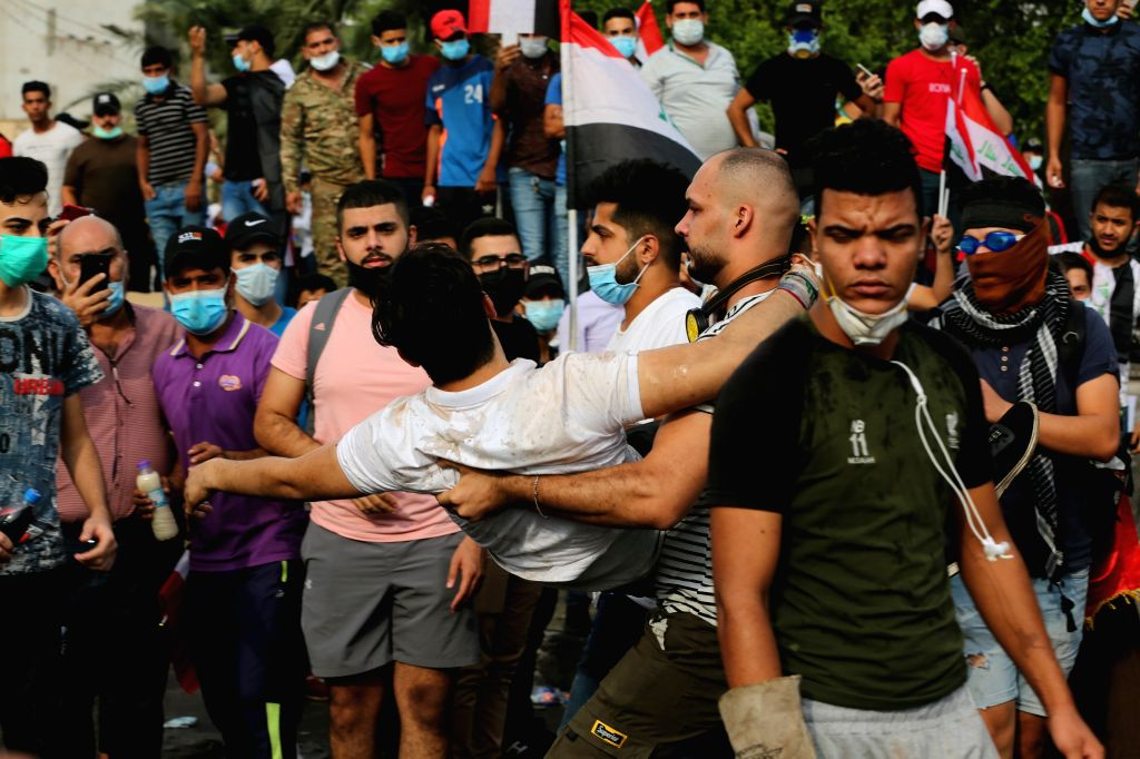 BAGHDAD, Oct. 27, 2019 - A wounded protester is carried away to safe place at Tahrir square in Baghdad, Iraq, on Oct. 27, 2019. The Iraqi authorities said on Sunday that the death toll from the new ...