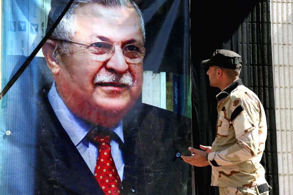 BAGHDAD, Oct. 4, 2017 - An Iraqi soldier looks at a picture of former President Jalal Talabani in Baghdad, Iraq, Oct. 4, 2017. Iraqi former President and the leader of Patriotic Union of Kurdistan ...
