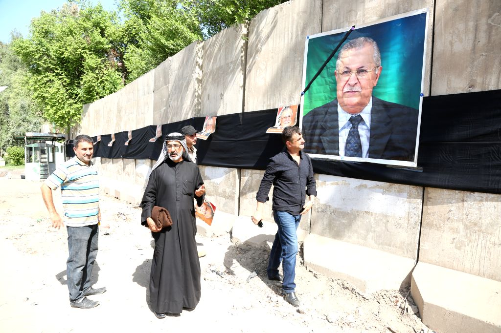 BAGHDAD, Oct. 4, 2017 - Iraqi people walk past a picture of former President Jalal Talabani in Baghdad, Iraq, Oct. 4, 2017. Iraqi former President and the leader of Patriotic Union of Kurdistan (PUK) ...