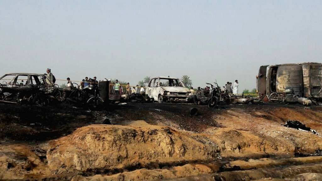 BAHAWALPUR, June 25, 2017 - Photo taken with a mobile phone shows rescuers and people gathering near burnout vehicles at the accident site in east Pakistan's Baahawalpur, a district in Punjab, on ...