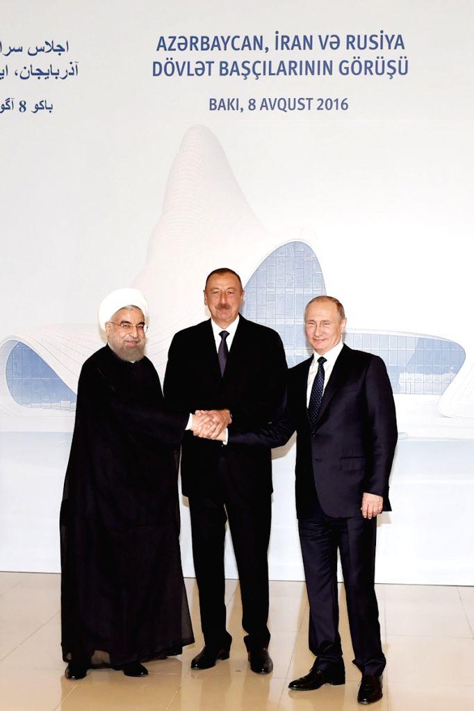 BAKU, Aug. 8, 2016 - Iranian President Hassan Rouhani (L), Azerbaijani President Ilham Aliyev (C) and Russian President Vladimir Putin shake hands during a trilateral meeting in Baku, Azerbaijan, ... - Hassan Rouhani