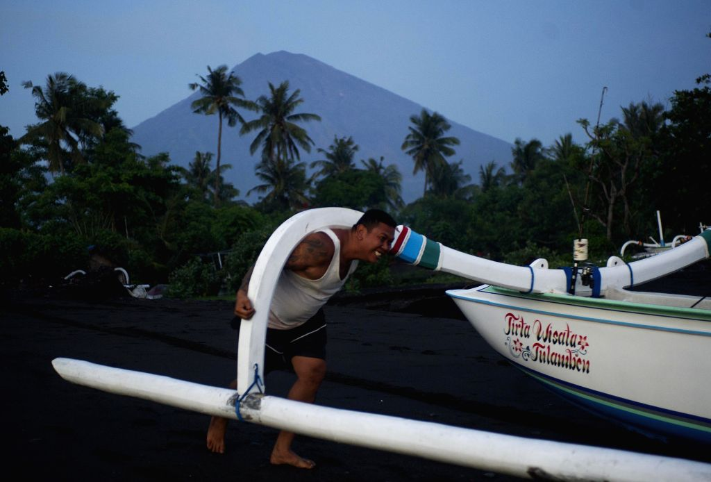 BALI, Dec. 4, 2017 - A Fisherman lifts up an outrigger boat into the sea with the background of Mount Agung volcano at Amed beach, Karangasem, Bali, Indonesia, Dec, 4. 2017. (Xinhua/Zulkarnain)