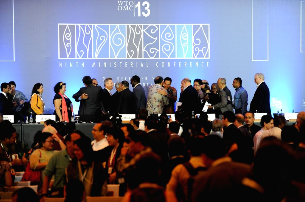Delegates celebrate during the closing ceremony of the Ninth Ministerial Conference of World Trade Organization at Bali Nusa Dua Convention Center, Indonesia, Dec.